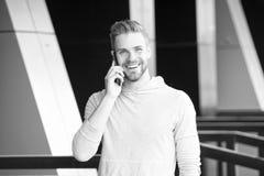 Quelles grandes actualités Homme avec le fond urbain de smartphone d'appel de barbe Smartphone heureux d'utilisation de sourire d photographie stock libre de droits