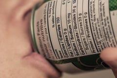 Quelqu'un buvant une boîte avec l'information nutritionnelle comme foyer Photo libre de droits