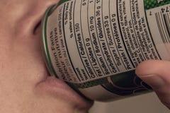 Quelqu'un buvant une boîte avec l'information nutritionnelle comme foyer Photos libres de droits