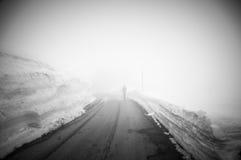 Quelqu'un marche sur la route menant par la campagne, la neige et le brouillard scéniques à la montagne de Grossglockner, Autrich Photographie stock libre de droits