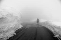 Quelqu'un marche sur la route menant par la campagne, la neige et le brouillard scéniques à la montagne de Grossglockner, Autrich Image stock