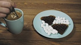 Quelqu'un met la table pour le petit déjeuner, le café et les gaufres avec des guimauves banque de vidéos