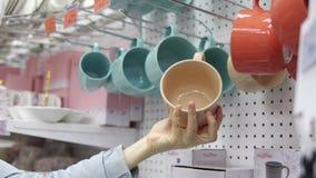 Quelqu'un sélectionne une grande tasse en céramique dans le supermarché banque de vidéos