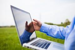 Quelqu'un travaillant avec un ordinateur portable Images stock