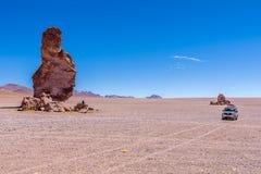Quelqu'un, une voiture et roche géante - Salar de Tara Image stock
