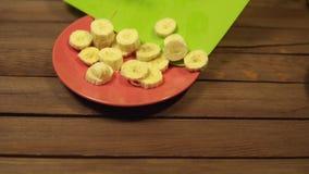Quelqu'un verse des tranches de banane d'une planche à découper dans un plat clips vidéos
