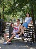Quelques ados datant en parc, belle fille et camarade s'asseyant sur un banc sur un fond brouillé naturel Photographie stock