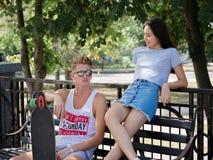 Quelques ados datant en parc, belle fille et camarade s'asseyant sur un banc sur un fond brouillé naturel Photos stock