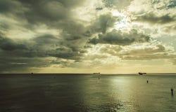 Quelques bateaux restent sur des ancres en mer sous les nuages Image stock
