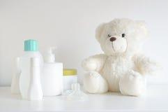 Quelques bouteilles de cosmétique, de parfum et de lotion sur une table blanche à côté d'un ours de nounours et d'une tétine Image libre de droits
