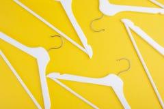 Quelques cintres en bois blancs sur un fond jaune Peut employer comme fond ou texture Configuration plate photo stock