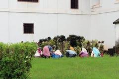 Quelques dames indiennes font du jardinage autour de la cathédrale de Se de vieux Goa image libre de droits