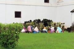 Quelques dames indiennes font du jardinage autour de la cathédrale de Se de vieux Goa photographie stock