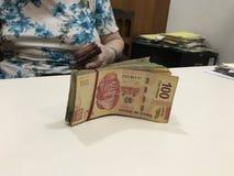 Quelques factures d'argent de peso mexicain empilées sur une table colorée beige photo stock