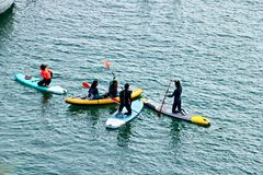 Quelques gar?ons et filles barbotent sur un conseil sur la surface de la mer photo libre de droits