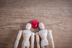 Quelques homme en bois de poupée avec du chocolat en forme de coeur Images libres de droits