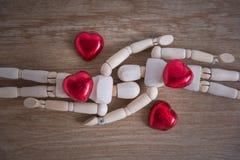 Quelques homme en bois de poupée avec du chocolat en forme de coeur Images stock