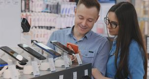 Quelques hommes et une femme se tiennent près d'un étalage avec des smartphones dans un magasin moderne de l'électronique et choi banque de vidéos