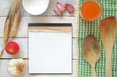 Quelques ingrédients de repice sur une table en bois blanche décorée d'une nappe verte Photos libres de droits