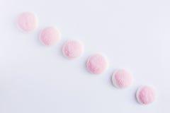 Quelques morceaux de sucrerie et de gelée roses et blanches est sur un CCB blanc Image libre de droits