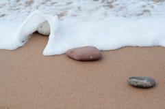Quelques petites pierres dans le sable et la vague venant, rivage de plage Photo libre de droits