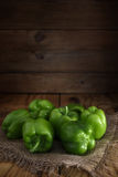 Quelques poivrons verts frais sur la toile de jute sur une table en bois Images stock