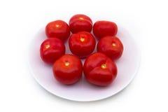 Quelques tomates rouges d'une plaque blanche Images stock