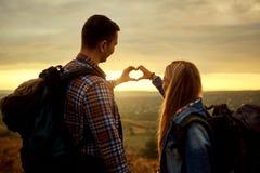 Quelques touristes avec des sacs à dos ont fait un symbole du coeur W Photo libre de droits