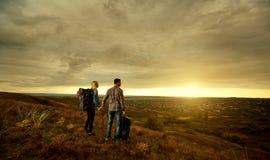 Quelques touristes avec des sacs à dos sur la nature au coucher du soleil Image libre de droits