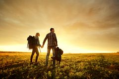 Quelques touristes avec des sacs à dos sur la nature au coucher du soleil Image stock