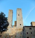 Quelques tours de San Gimignano en Italie contre le ciel bleu profond, allumées par le coucher de soleil pâle image stock