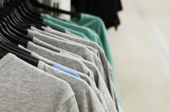 Quelques vêtements utilisés accrochant sur un support sur un marché aux puces Fond de robe Foyer sélectif images libres de droits