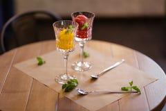 Quelques verres à vin en cristal chers complètement de crème glacée de fruit Sorbet coloré avec la menthe décorative sur treillag Image stock