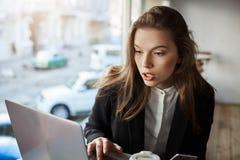 Quem deixou a resposta má sobre minha empresa Retrato interno da menina à moda incomodada e confundida que senta-se no café, trab imagem de stock