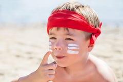 Quem são mim? Proteção solar & x28; lotion& x29 do bronzeado; está na cara do menino do moderno antes de bronzear-se durante féri Imagem de Stock