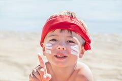 Quem são mim? Proteção solar & x28; lotion& x29 do bronzeado; está na cara do menino do moderno antes de bronzear-se durante féri Fotografia de Stock