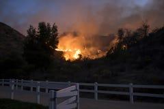 Quemaduras del fuego más allá del parque de vecindad con la cerca en primero plano durante el fuego de California imágenes de archivo libres de regalías