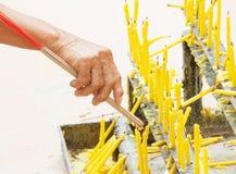 Queme los palillos del incienso con la vela y la vieja mano asiática Foto de archivo