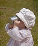 Quenching the Thirst. Little old-fashioned girl drinking milk from a tin cup Royalty Free Stock Images