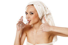 Quenching thirst. Woman with a towel on her head drinking water from a glass and showing thumb up Royalty Free Stock Images