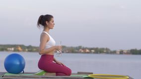 Quenching thirst, young happy sports girl drinks mineral clear water from bottle while doing fitness and enjoy rest in. Nature on river against sky stock video footage