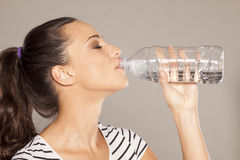 Quenching thirst. Young woman drinks water  from a plastic bottle Royalty Free Stock Photos