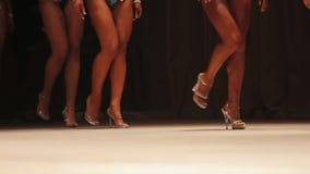 Quepa las piernas bronceadas de los modelos hermosos de la aptitud que caminan en etapa en zapatos del tacón alto metrajes