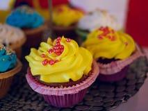 Queque amarelo geado com muitos queques coloridos fotos de stock royalty free