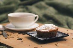 Queque caseiro com açúcar pulverizado em uma placa preta e em um copo branco do chá com aditivos naturais em uma bandeja de madei fotografia de stock royalty free