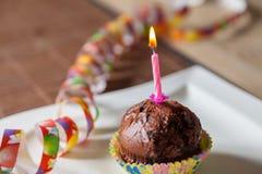 Queque com uma vela do aniversário na placa Fotos de Stock