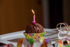 Queque com uma vela do aniversário na placa Fotos de Stock Royalty Free