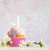 Queque cor-de-rosa do manteiga-creme com flor e vela Imagens de Stock