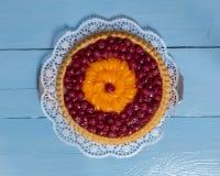 Queque de frutas con las cerezas y las mandarinas en la madera azul Fotografía de archivo libre de regalías