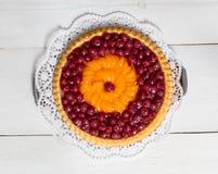 Queque de frutas con las cerezas y las mandarinas en la madera blanca Imagen de archivo libre de regalías